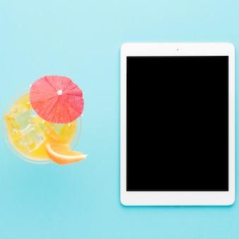 Tablet und cooles cocktail auf hellem hintergrund