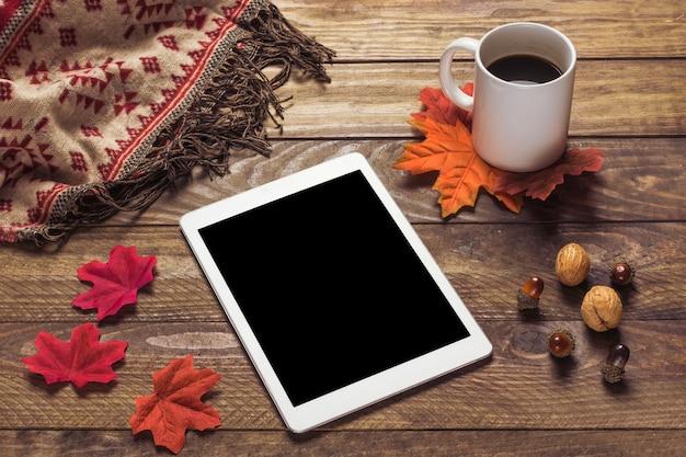 Tablet und decke in der nähe von blättern und kaffee