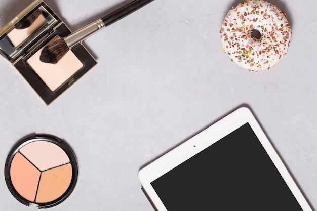 Tablet und donut in der nähe von gesichtspuder