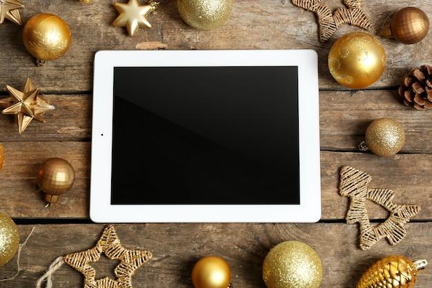 Tablet und weihnachtsdekor auf holztisch