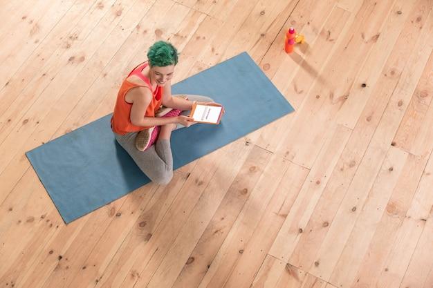 Tablet verwenden. grünhaarige frau mit grauen leggings sitzt auf blauer sportmatte und benutzt tablet