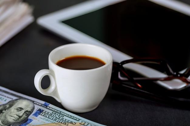 Tabletnotizblock, gläser und espressokaffeetasse im bürokassenamerikaner von us 100 dollar