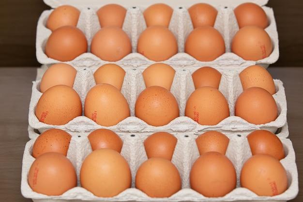 Tablett mit braunen und biologischen hühnereiern auf dem tisch