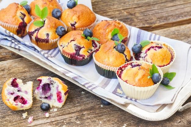 Tablett mit cupcakes mit frischen heidelbeerbeeren und blättern auf holztisch