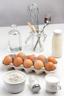 Tablett mit eiern und schüssel mehl. zwei flaschen milch und wasser. metall schneebesen und löffel im glas.