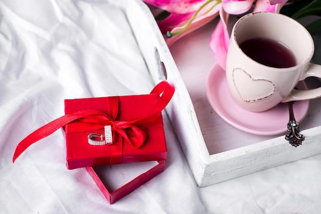 Tablett mit einer tasse heißen tee im bett