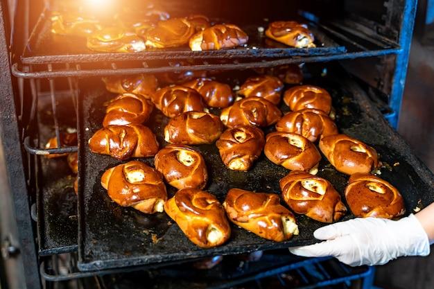 Tablett mit frischen brötchen oder brötchen. heiße backwaren aus dem ofen. bäckerei oder brotfabrik. die bäckereiproduktion.