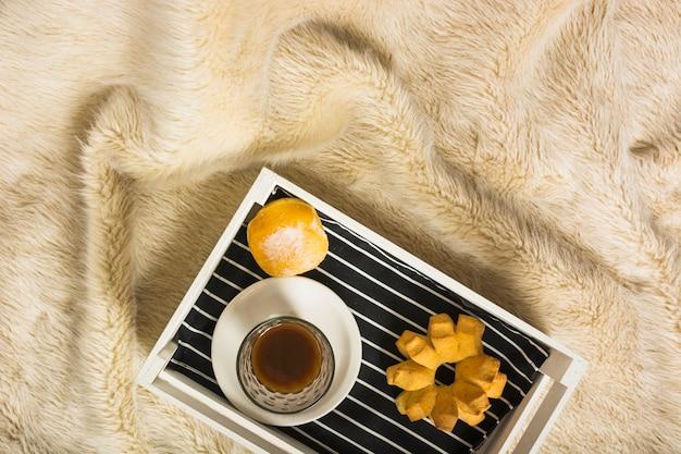 Tablett mit frühstück auf pelzdecke