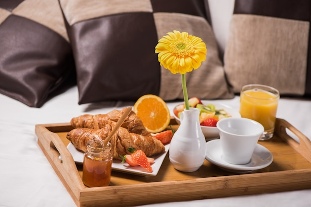 Tablett mit frühstücksessen auf dem bett in einem schlafzimmer