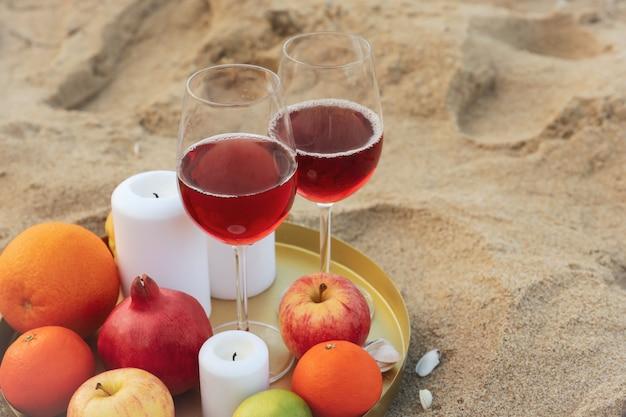 Tablett mit gläsern wein, obst und kerzen am sandstrand