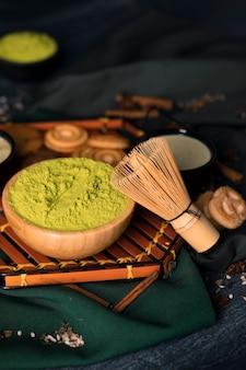 Tablett mit grünem pulver auf schüssel für tee