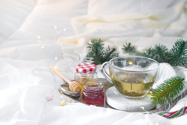 Tablett mit honig und eine tasse heißen tee im bett, faulen morgen, warme winterstimmung