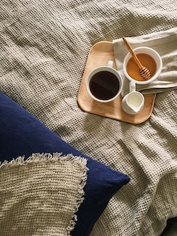 Tablett mit honig und einer tasse heißen tee im bett, fauler morgen, warme winterstimmung