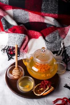 Tablett mit honig und einer tasse heißen tee im bett,