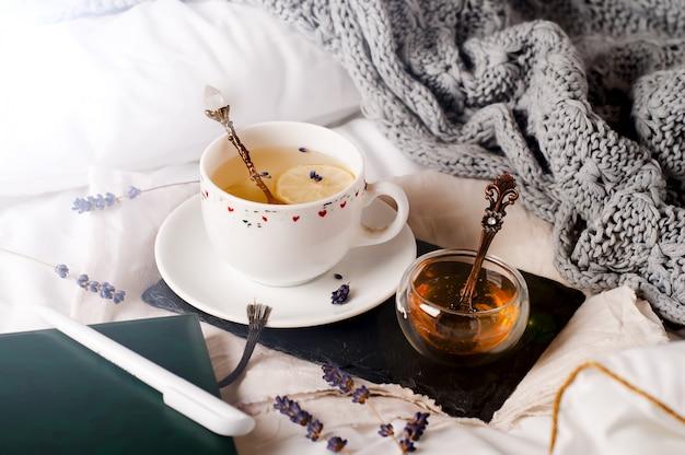 Tablett mit honig und einer tasse heißen tee im bett