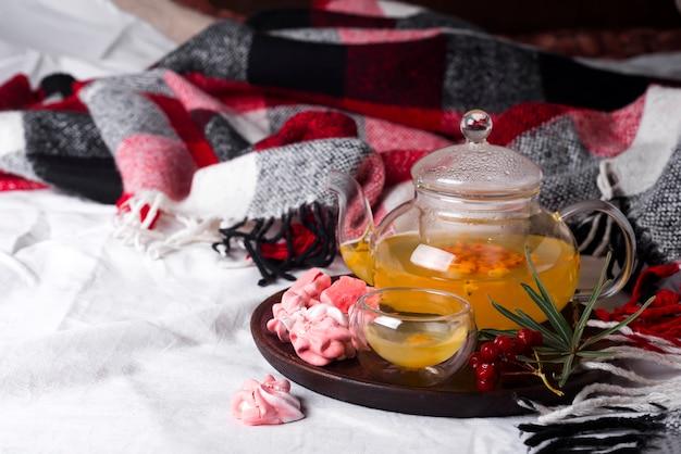 Tablett mit honig und einer tasse heißen tee mit rosa meringues im bett,