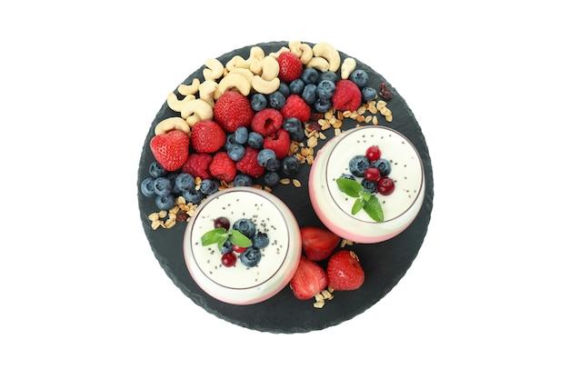 Tablett mit joghurt und zutaten auf weißem hintergrund