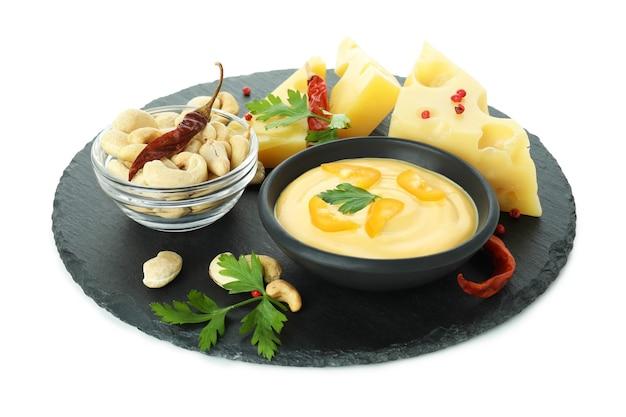 Tablett mit käsesauce und snacks auf weißem hintergrund