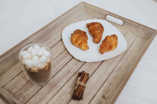 Tablett mit kaffee mit marshmallow-croissants und zimt