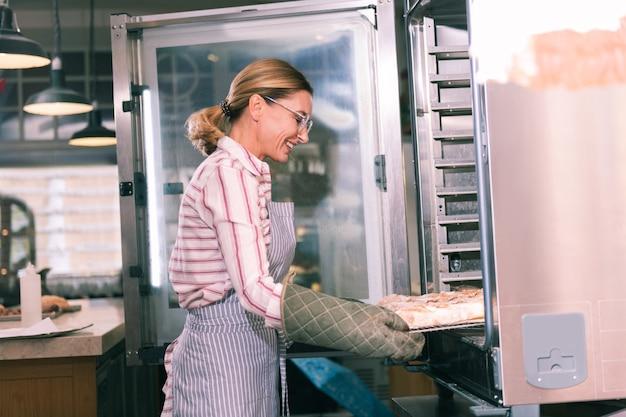 Tablett mit kuchen. strahlender arbeiter der bäckerei, der ofen öffnet und tablett mit erstaunlichem obstkuchen herausnimmt