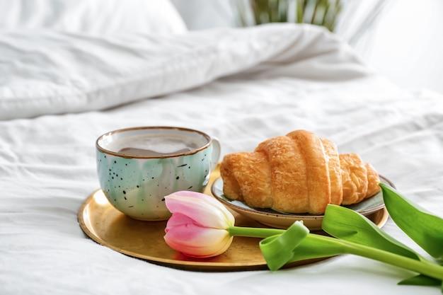 Tablett mit leckerem croissant und tasse kaffee auf dem bett