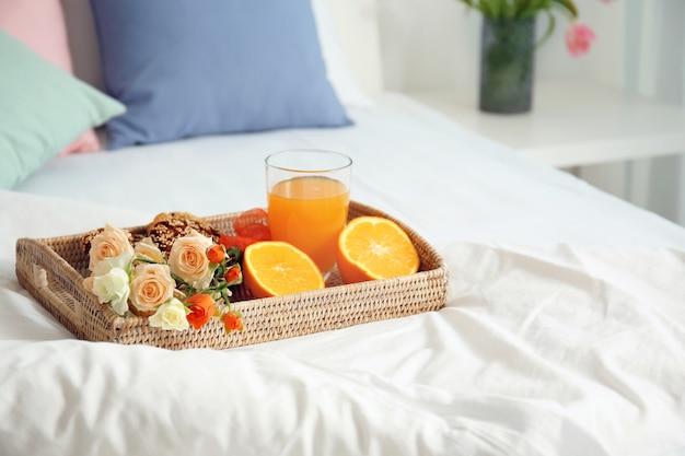 Tablett mit leckerem frühstück auf bequemem bett zu hause