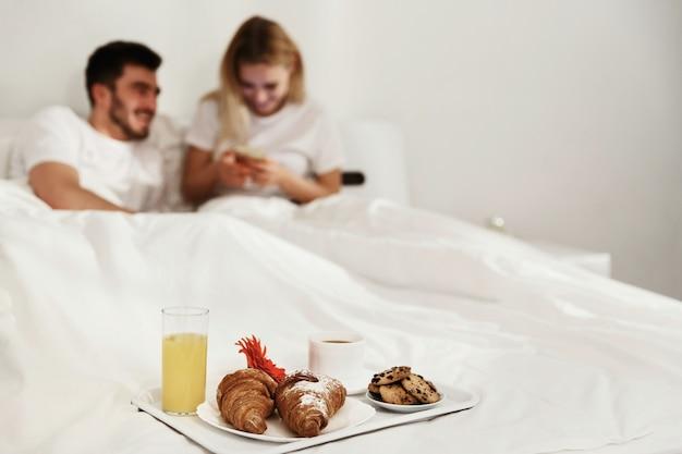 Tablett mit leckerem kaffee, croissants, saft und keksen steht auf dem bett, bevor ein paar auf das telefon schaut