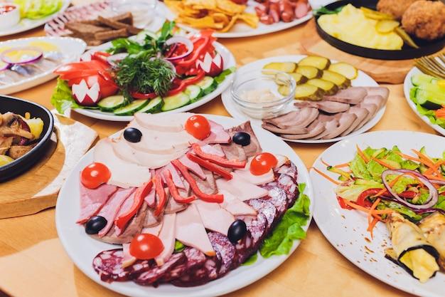 Tablett mit leckeren salami, stücke schinken, wurst und salat. fleischplatte mit auswahl auf dem tisch.