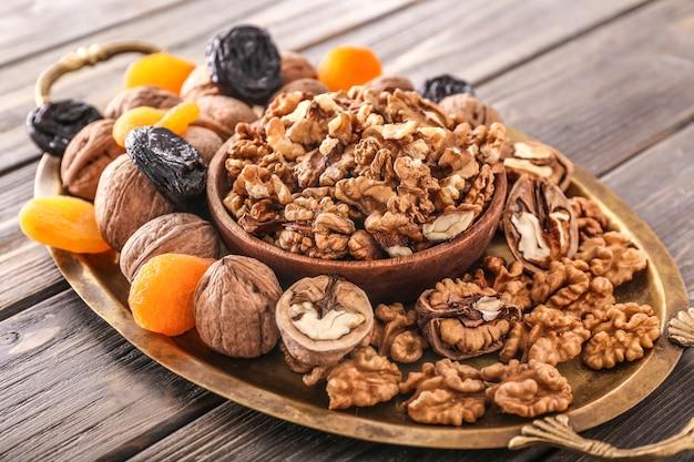 Tablett mit leckeren walnüssen und getrockneten früchten auf holz