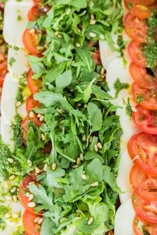 Tablett mit mozzarella, tomaten und salat für ein buffet