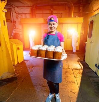 Tablett mit osterkuchen an der hintergrundtextur der industriebäckerei. frau hält tablett mit frischer backwaren. Premium Fotos