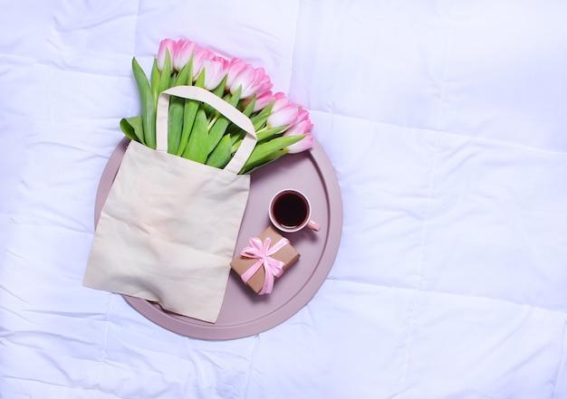 Tablett mit tasse kaffee, geschenkbox und öko-tasche mit rosa tulpen auf weißem laken auf dem bett.