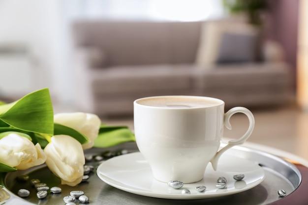 Tablett mit tasse kaffee und schönen blumen auf dem tisch