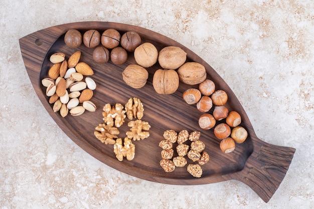 Tablett mit verschiedenen nüssen und schokoladenbällchen auf marmor