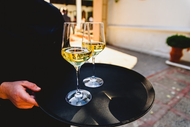 Tablett mit zwei gläsern champagner von einem kellner gehalten.