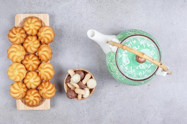 Tablett voll hausgemachter kekse neben teekanne und einer kleinen schüssel schokoladenpilze auf marmorhintergrund. hochwertiges foto