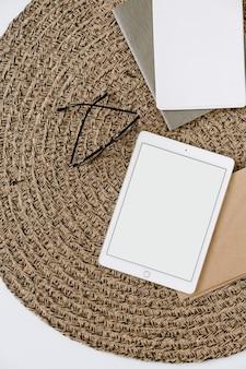 Tablettblock mit leerem modellkopierraumbildschirm, zwischenablage, umschlag auf rattanhintergrund