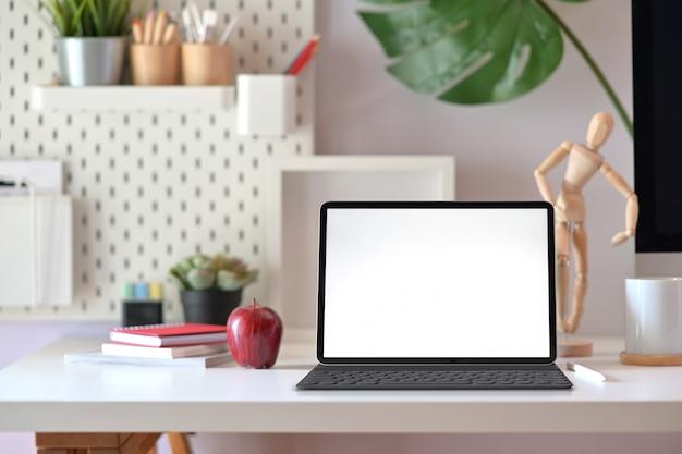 Tablette des leeren bildschirms auf moderner unbedeutender schreibtischarbeitsplatztabelle und kopienraum