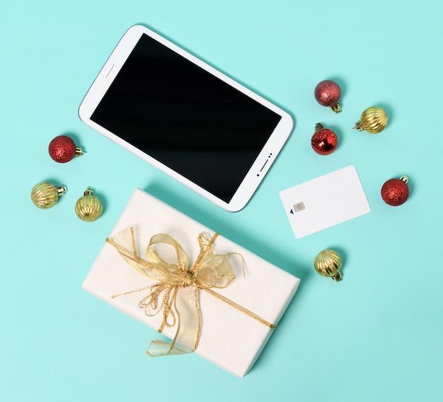 Tablette, geschenk, kreditkarte und weihnachtskugeln auf einer minze