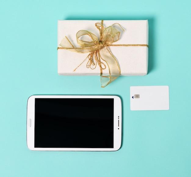 Tablette, geschenk und kreditkarte auf einer minze