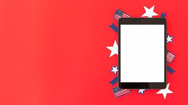 Tablette mit dekorativen elementen der amerikanischen flagge auf roter oberfläche