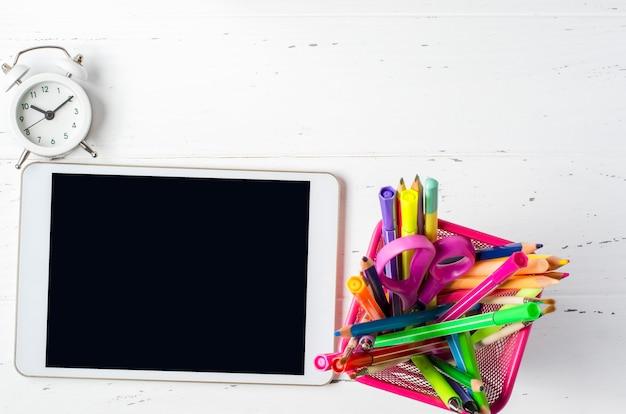 Tablette mit einem leeren bildschirm und büromaterial auf einem weißen hölzernen hintergrund. konzept-app für schulkinder oder online-lernen für kinder. speicherplatz kopieren