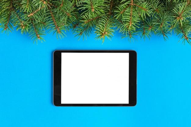 Tablette mit leerem bildschirm auf der blauen pastellfarbe. draufsicht mit weihnachtsdekor