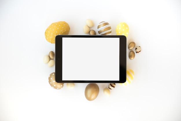 Tablette mit leerem bildschirm auf ostereiern
