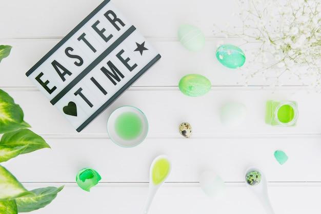 Tablette mit ostern-zeittitel nahe eiern zwischen blumenzweig und dosen mit farbstoffflüssigkeit