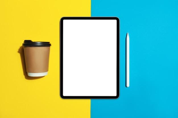 Tablette mit weißem bildschirm auf augenfarbenhintergrund mit bleistift