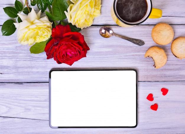 Tablette mit weißem schirm, tasse schwarzen kaffee und blumenstrauß von rosen
