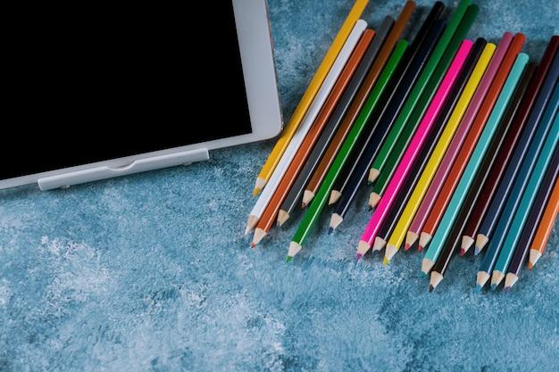 Tablette neben buntstiften auf blauem hintergrund,
