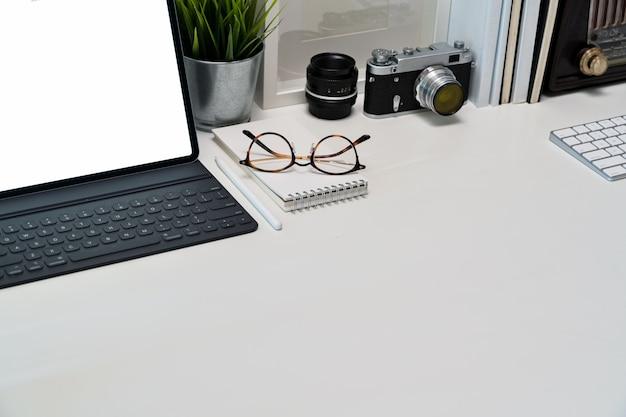 Tablette, plakat, bücher und weinlesekamera des modells des leeren bildschirms auf arbeitsplatz