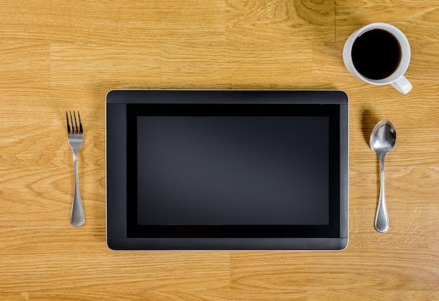 Tablette über hölzerner tabelle mit löffel, gabel und kaffeetasse